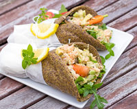 Healthy salmon wraps. Grain free alternative wrap filled with vegetables, herbs and salmon. Served wrapped up in parchment paper Stock Photos