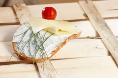 Healthy sandwich. A slice of rye bread topped with quark, cheese, chives and a cherry tomato on wooden background Stock Photography