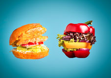 The healthy sandwich with fresh pepper, onion, salad lettuce and unhealthy harmful hamburger. Healthy sandwich with fresh pepper, onion, salad lettuce and Stock Images