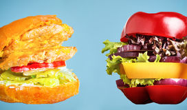The healthy sandwich with fresh pepper, onion, salad lettuce and unhealthy harmful hamburger Stock Image