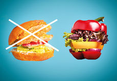 The healthy sandwich with fresh pepper, onion, salad lettuce and unhealthy harmful hamburger Stock Images