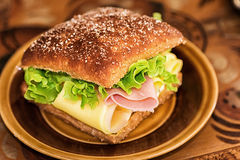 Healthy sandwich with lettuce, cheese and ham. On a brown plate and background Royalty Free Stock Photography
