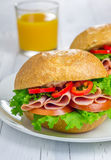 Healthy sandwiches with ham and a glass of orange juice. On the wooden table Royalty Free Stock Photography