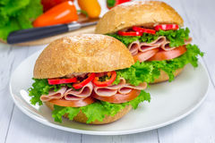 Healthy sandwiches with ham. And a wooden board with vegetables on background Royalty Free Stock Images