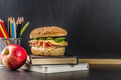 Healthy school food concept, lunch with apple, sandwich, books a. Nd alarm clock on chalkboard background copy space royalty free stock image
