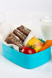 Healthy school lunch. Lunchbox filled with healthy bread, vegetables and fruit with a glass of milk Stock Photos