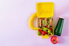 Healthy school lunch box with beef sandwich and fresh vegetables. Bottle of water and fruits on pink background. Top view. Flat lay stock images