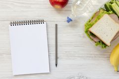 Healthy school lunch box with notebook and pencil on white woode. N background, flat lay. From above Royalty Free Stock Images