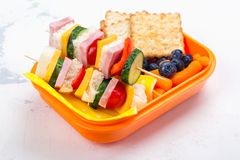 School lunch box. Healthy school lunch box with sandwich kabobs, yogurt, juice, fruits and berries stock photos