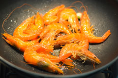 Healthy seafood cooking shrimp on wok. Healthy seafood cooking golden shrimp in a wok or stir-fry pan Stock Images
