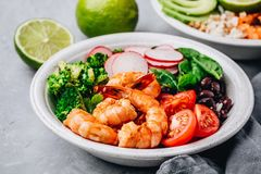 Spicy Shrimp Burrito Buddha Bowl with wild rice, spinach, radish, tomatoes, black beans and broccoli. Healthy seafood lunch. Spicy Shrimp Burrito Buddha Bowl stock images