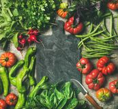 Healthy vegan food background with seasonal vegetables and greens. Healthy seasonal food cooking background. Flat-lay of fresh vegetables and greens over grey stock photo