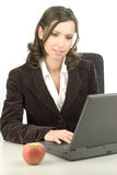 Healthy secretary. Young woman typing on a laptop with an apple on the desk Royalty Free Stock Photography
