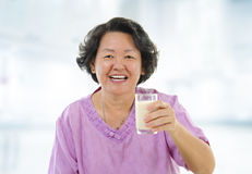 Healthy Senior Asian and soy milk. Senior Asian woman holding a glass of soy milk at home Stock Image