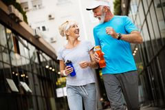Healthy senior, couple jogging in the city at early morning with sunrise. Healthy senior couple jogging in the city at early morning royalty free stock photos