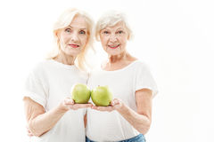 Healthy senior ladies inspiring to eat vitamins. Take care of your health. Waist up portrait of cheerful old women holding green apples and showing it to camera Stock Photography