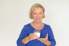 Healthy senior lady drinking fresh milk. Healthy senior lady drinking a glass of chilled fresh milk with a smile of appreciation and enjoyment as she looks at Royalty Free Stock Photography