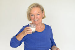 Healthy senior lady drinking fresh milk. Healthy senior lady drinking a glass of chilled fresh milk with a smile of appreciation and enjoyment as she looks at Royalty Free Stock Photos