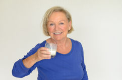 Healthy senior lady drinking fresh milk. Healthy senior lady drinking a glass of chilled fresh milk with a smile of appreciation and enjoyment as she looks at Stock Photo