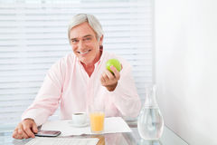 Healthy senior man holding apple Stock Photography