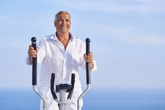 Healthy senior man working out. On gym treadmill machine at modern home terace with ocean view royalty free stock images