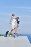 Healthy senior man working out. On gym treadmill machine at modern home terace with ocean view stock photography