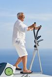 Healthy senior man working out. On gym treadmill machine at modern home terace with ocean view stock images