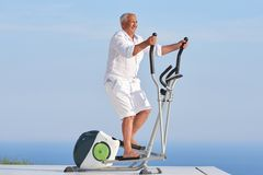 Healthy senior man working out. On gym treadmill machine at modern home terace with ocean view stock image