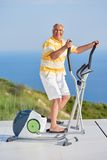 Healthy senior man working out. On gym treadmill machine at modern home terace with ocean view royalty free stock photography
