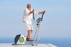 Healthy senior man working out. On gym treadmill machine at modern home terace with ocean view royalty free stock image