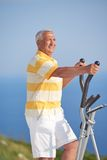 Healthy senior man working out. On gym treadmill machine at modern home terace with ocean view stock photo