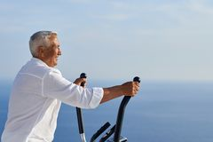 Healthy senior man working out. On gym treadmill machine at modern home terace with ocean view royalty free stock photo