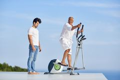 Healthy senior man working out. Healthy senior men working out on gym treadmill machine at modern home terace with ocean view royalty free stock photo
