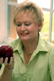 Healthy senior woman with apple. A senior woman holding and looking at an apple by a sunny window Royalty Free Stock Photography