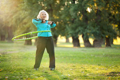 Healthy Senior Woman doing Exercises in Nature. 70 years old Senior Woman doing Exercises with the Plastic Hoop at the Green Meadow in the Bright Autumn Evening Stock Photography