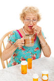 Healthy Senior Woman Takes Medication. Healthy senior woman taking her daily doses of medicine.  White background Stock Images