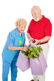 Healthy Seniors Recycle. Seniors buying healthy produce and using recycleable grocery bags.  Isolated on white Royalty Free Stock Photography
