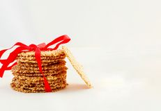 Healthy Sesame crisps cookies with red ribbon. White background. royalty free stock photos