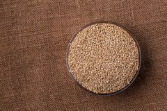 Healthy sesame seeds in a glass bowl. Healthy sesame seeds in a glass jar from above on brown linen background with space for text. Vegan protein source stock photos