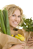 Healthy Shopping. Smiling woman carries fruits and vegetables in brown paper bags royalty free stock photos