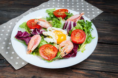 Healthy Shrimp and Arugula Salad with Tomatoes on a wooden table Royalty Free Stock Images
