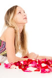 Healthy skin, a beautiful girl lies in rose petals Royalty Free Stock Photos
