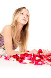 Healthy skin, a beautiful girl lies in rose petals Stock Photos