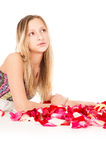 Healthy skin, a beautiful girl lies in rose petals Royalty Free Stock Images