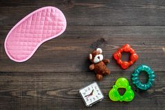Healthy sleep for children. Sleep mask, alarm clock, toys on dark wooden background top view copyspace Stock Images