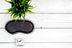 Healthy sleep concept. Sleep mask, plant, alarm clock on white wooden background top view copyspace Royalty Free Stock Photography