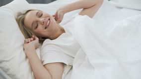 Healthy sleep on orthopedic mattress, happy teenage girl waking up with smile