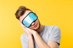 Healthy sleep rest relaxation man eye mask. Healthy peaceful sleep rest relaxation. Coziness lifestyle habit. Young man eye mask on. Hands pressed together head stock photography