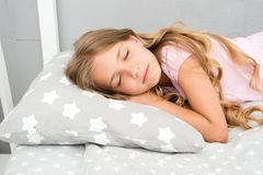 Healthy sleep tips. Girl sleep on little pillow bedclothes background. Kid long curly hair fall asleep pillow close up. Choose proper pillow to relax. Cute royalty free stock images