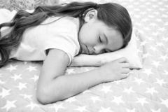 Healthy sleep tips. Girl sleeps on little pillow bedclothes background. Girl child long hair fall asleep pillow close up. Quality of sleep depends on many stock photo